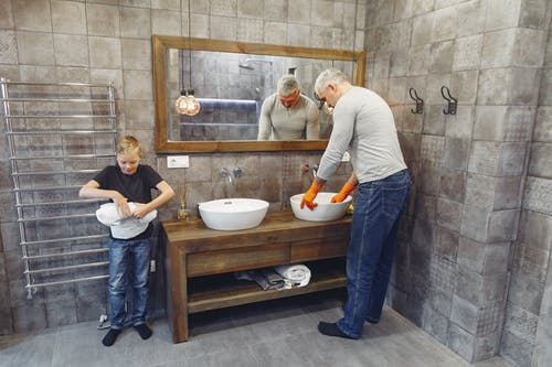 Grey haired dad with beard in orange rubber gloves and small boy cleaning bathroom together