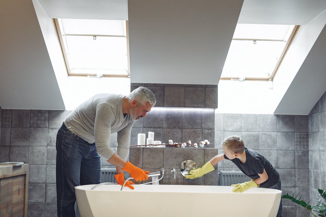 Side view of grey haired dad with beard in orange rubber gloves cleaning bathroom together with son