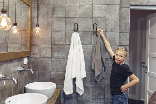 Small boy with blond hair hanging up towel in spacious bathroom while looking at camera