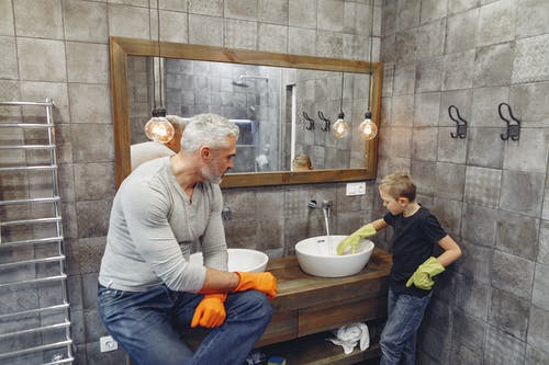 Father with child cleaning sink in bathroom