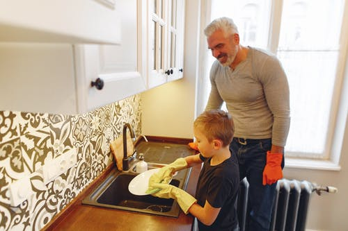 Dad with kid dishwashing at kitchen
