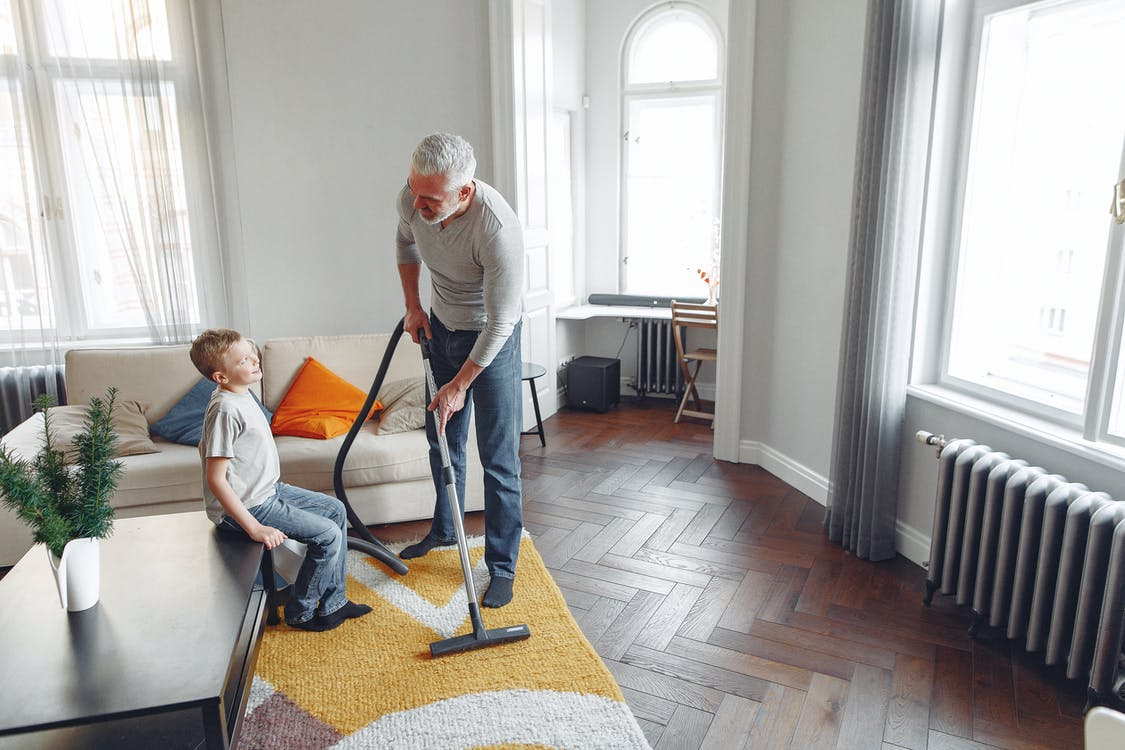 From above of happy grey haired man with beard vacuum cleaning while talking with kid