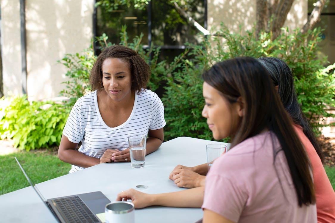 Mulher Com Camisa Listrada De Branco E Preto Sentada Ao Lado Da Mulher Com Camisa Rosa