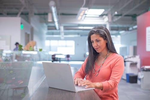Woman in Orange Long Sleeve Shirt Using Macbook Pro