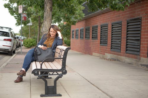 Woman in Blue Denim Jeans Sitting on Black Metal Bench