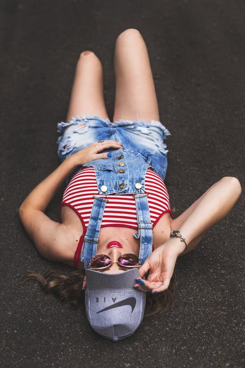 From above of young slim female millennial in stylish denim overall and sunglasses touching cap while lying on asphalt ground