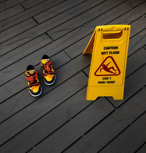Stylish sneakers on wooden floor near caution board