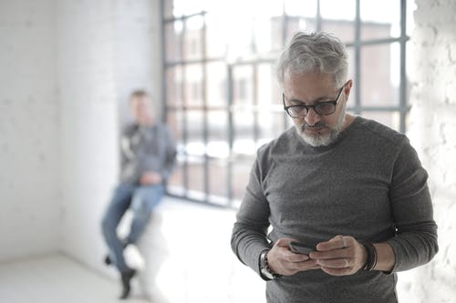 Serious middle aged coworker surfing internet on smartphone