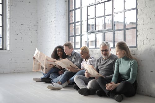 Multiethnic colleagues reading newspaper while sitting on floor