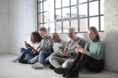 Diverse people surfing internet on smartphone in afternoon