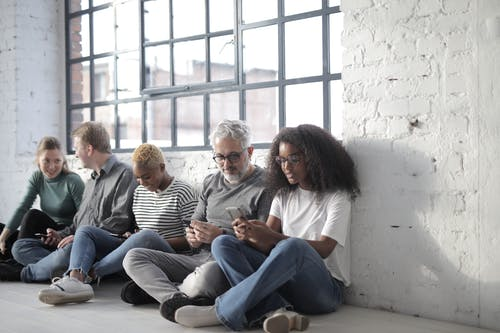 Happy multiethnic coworkers immersed in social media using smartphones