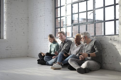 Content multiracial coworkers sitting on floor with smartphones