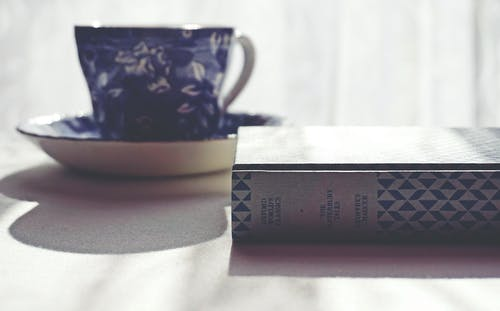 Floral Ceramic Mug Beside A Book