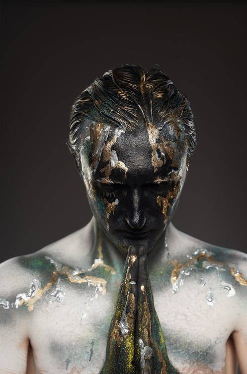 Male model with body art and hands in pray gesture