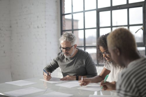 Concentrated multiracial people of different ages sitting at table near while writing on sheets of paper with pen in afternoon