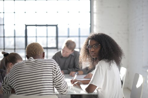 Serious African American female worker writing with pen on sheet of paper while sitting at table near diverse partners and looking at camera in sunlight