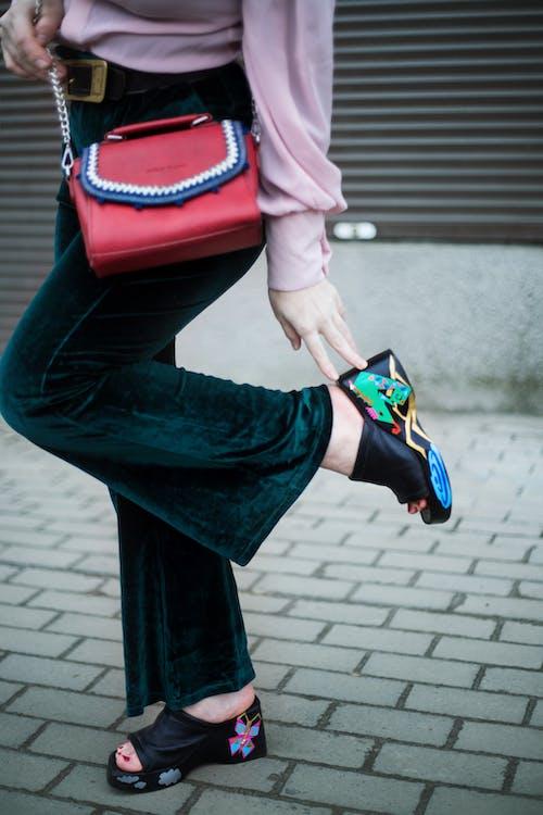 Crop stylish woman touching shoe heel on street