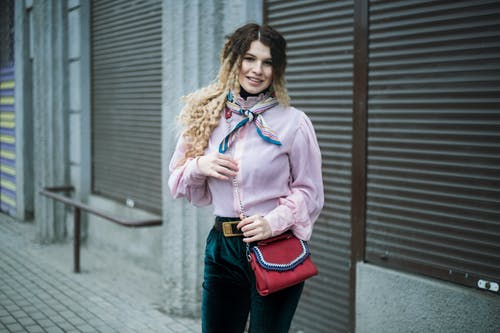 Positive stylish woman on street near building wall