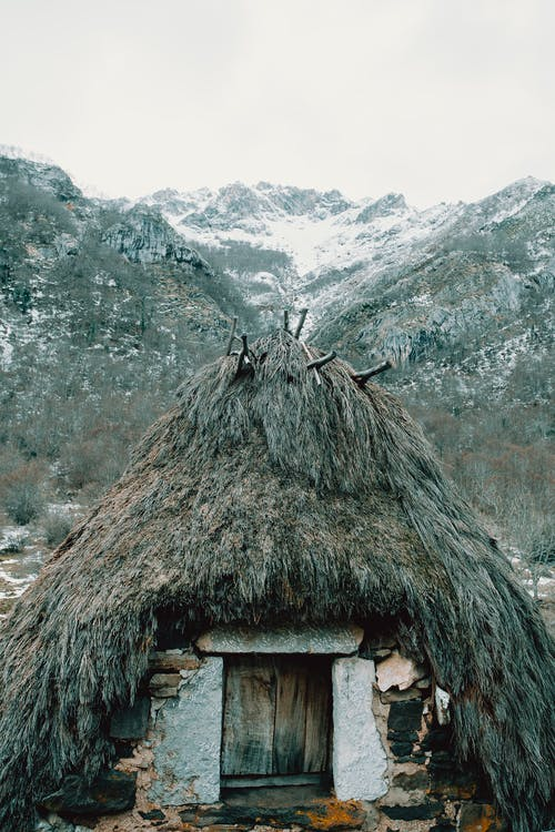 Old aboriginal stone wigwam with thatched roof located on snowy mountainous terrain in winter