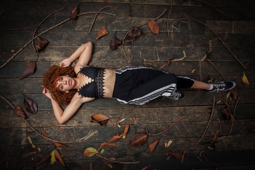 Photo Of Woman Lying On Wooden Flooring