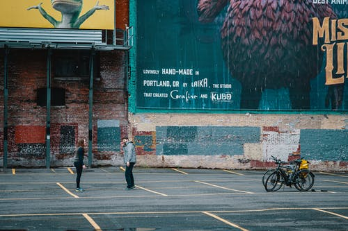 Side view full length faceless man and woman in outerwear standing face to face on asphalt ground near bicycles against shabby brick wall