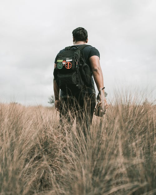 Man in Black T-shirt and Black Backpack Standing on Brown Grass Field