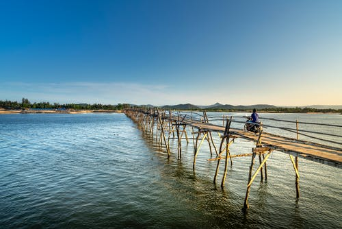Back view full body faceless person riding bicycle along narrow fragile pedestrian bridge on thin wooden legs above rippling river on clear summer day