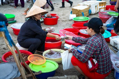 Asian woman selling seafood on street market