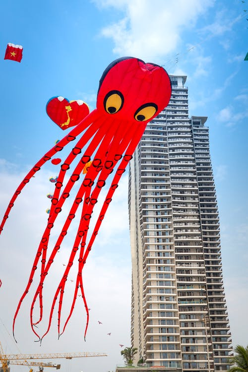 From below red octopus kite flying high in sky against contemporary tall skyscraper