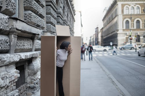 African American woman peeking out of cardboard box on sidewalk