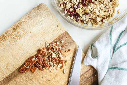 Photo Of Chopped Pecans On Wooden Chopping Board