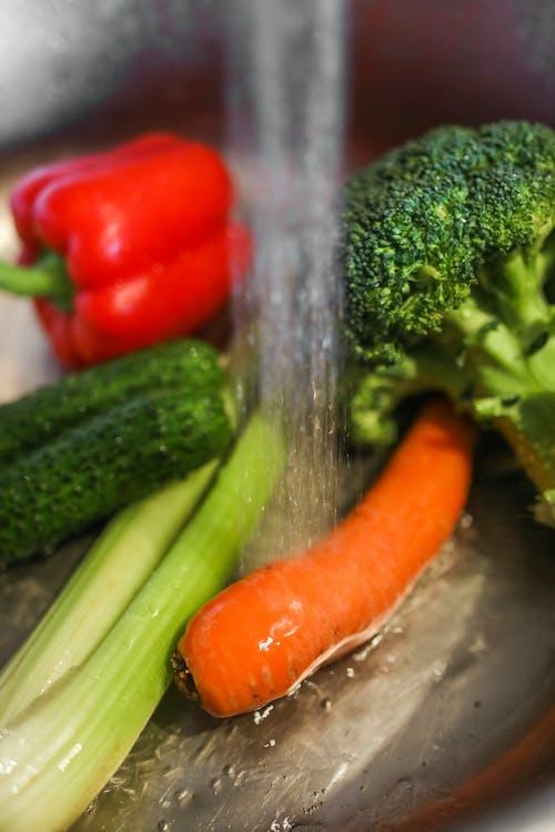 Fresh vegetables under running water in metal bowl