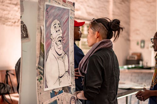Ethnic woman observing creative portrait on exhibition