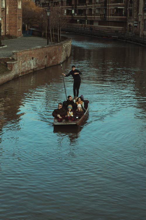 Man in Black Jacket Riding on Brown Boat on Water