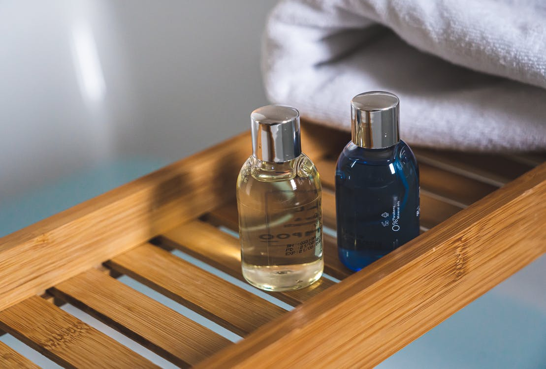 Three Blue Glass Bottles on Brown Wooden Table