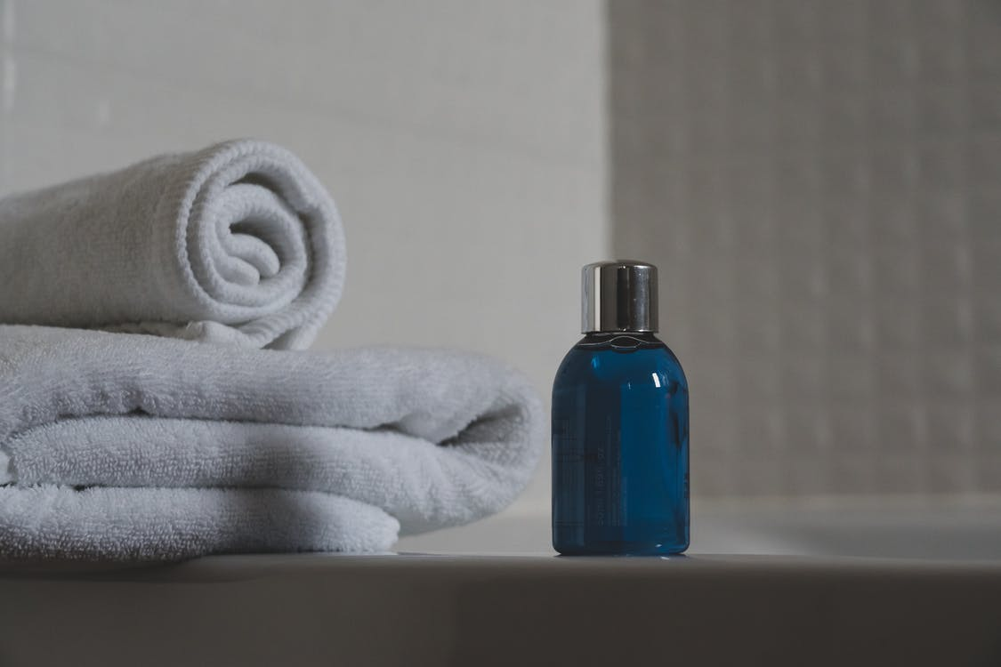Blue Glass Bottle Beside White Towel
