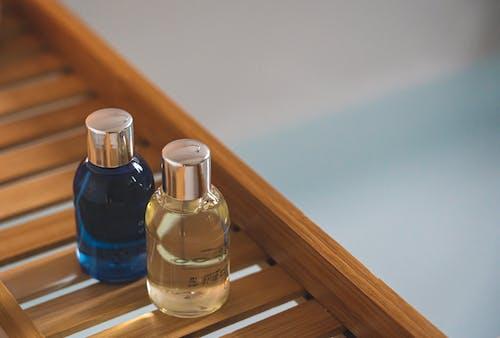 Botella De Vidrio Transparente Sobre Mesa De Madera Marrón