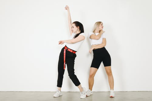 Young female dancers in sportswear and sneakers making dancing movements while standing on concrete floor in studio near white wall