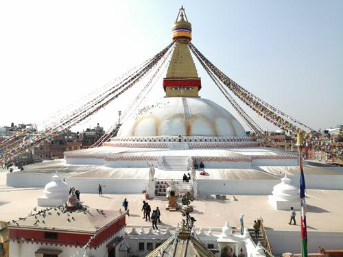 Spherical Boudhanath with white walls and decorative flags strained from spire located in Kathmandu Nepal