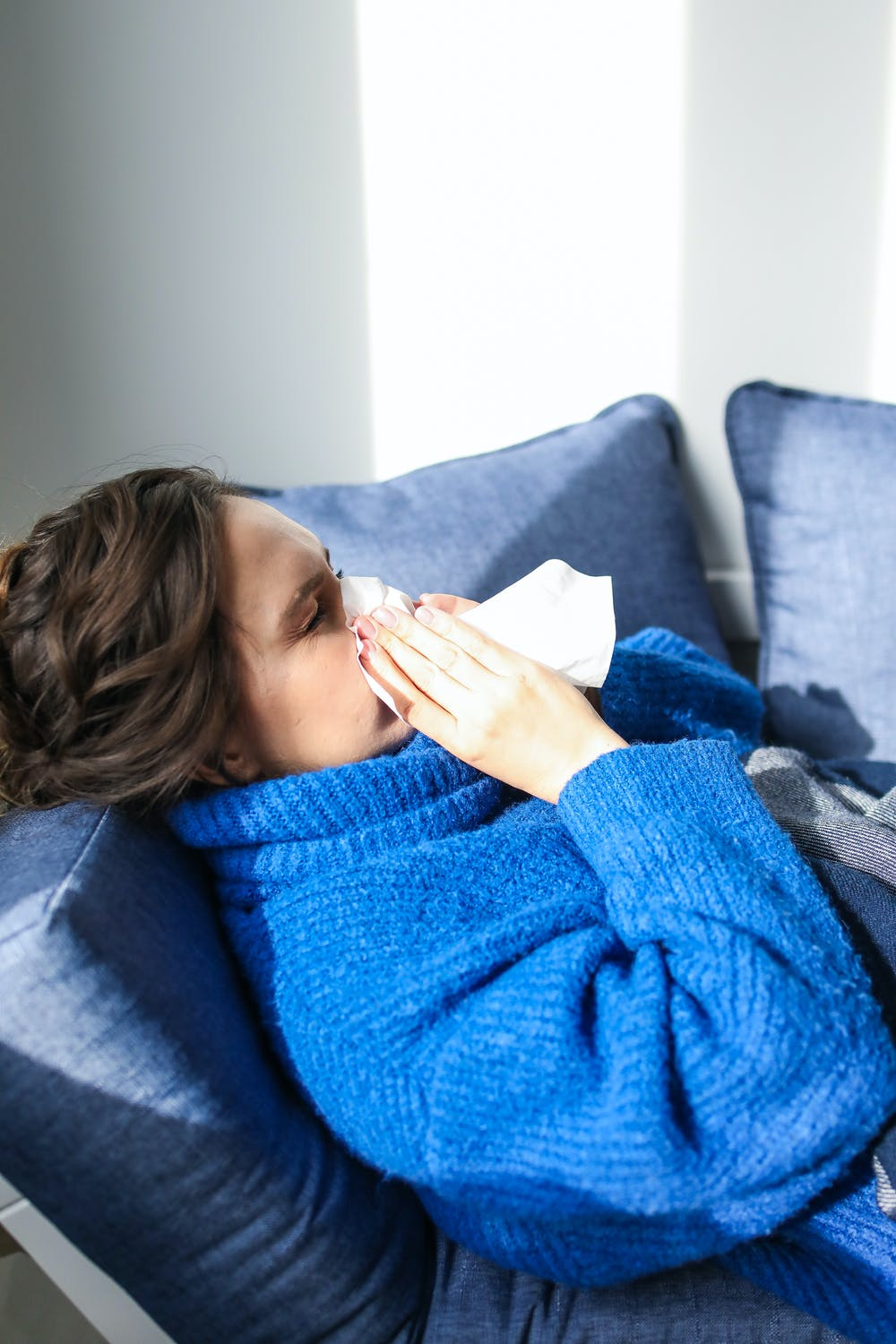 woman in blue sweater blowing her nose