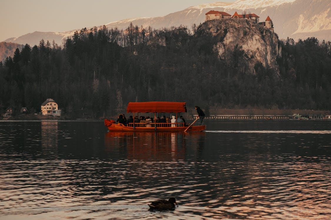 人们骑着小船在山附近的湖上