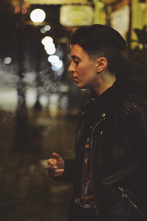 Man in Black Leather Jacket Standing during Night Time