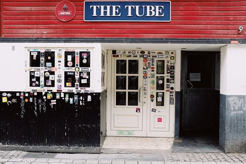 Exterior of closed pub with blue sign above entrance decorated with graffiti and colorful stickers