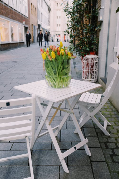 Colorful tulips placed in vase on white cafe terrace