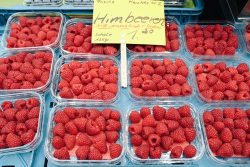 Plastic containers with fresh raspberries on market stall
