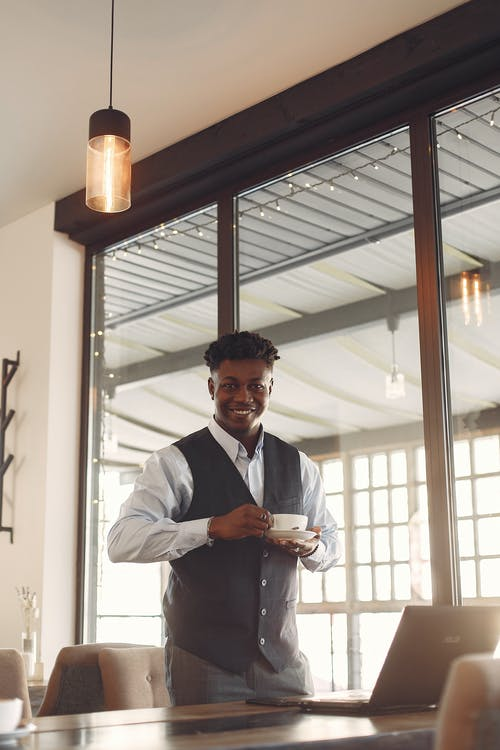 Positive elegant ethnic entrepreneur drinking coffee while standing near table in cafe