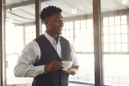 Smiling young ethnic man drinking coffee in cafe near window