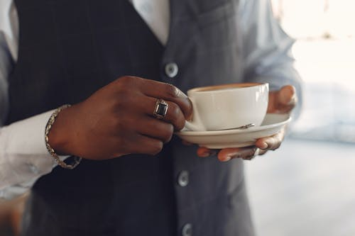 Crop unrecognizable African American man in formal suit holding cup of fresh coffee in hands while standing in modern light cafe