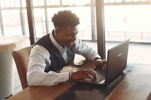 Positive young ethnic businessman working on laptop while sitting in cafe