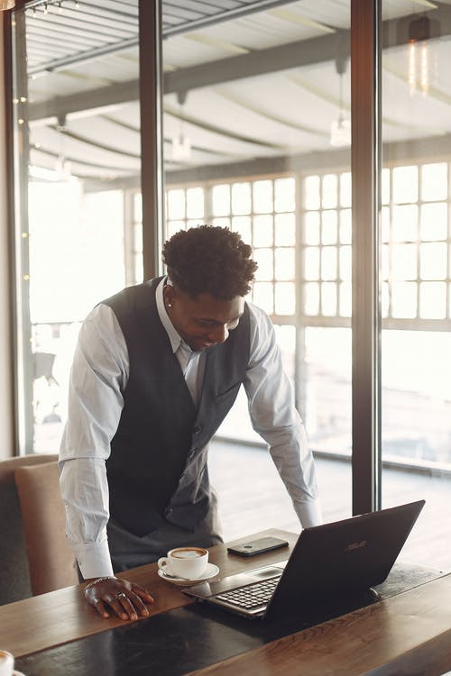 Cheerful young ethnic male entrepreneur working with laptop while standing near table in cafe
